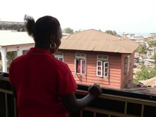 Marion Kargbo stands at a balcony in Freetown, Sierra Leone